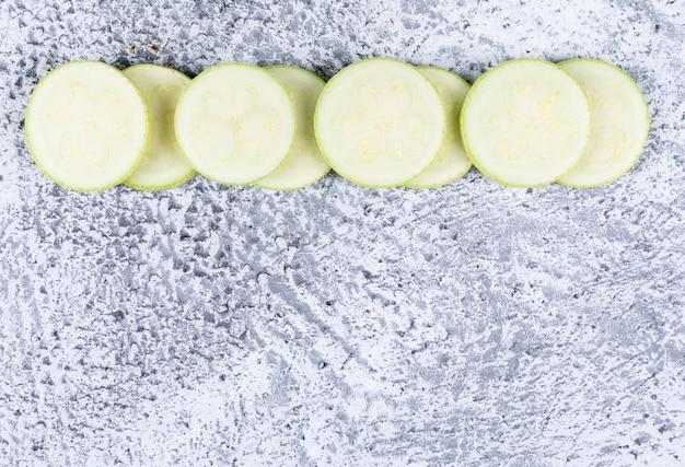 Plat lag gesneden courgettes op grijze getextureerde tafel.