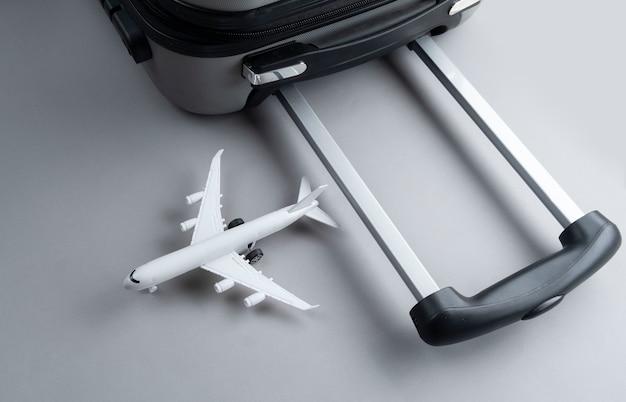 Plat lag grijze koffer met mini vliegtuig op grijs