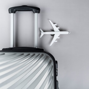 Plat lag grijze koffer met mini vliegtuig. reis concept