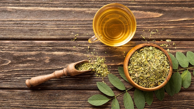 Plat lag groene bladeren en kopje thee