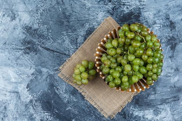 Plat lag groene druiven in mand op grunge en stuk zak achtergrond. horizontaal
