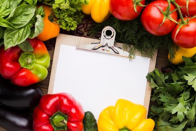 Plat lag groentenassortiment met leeg klembord