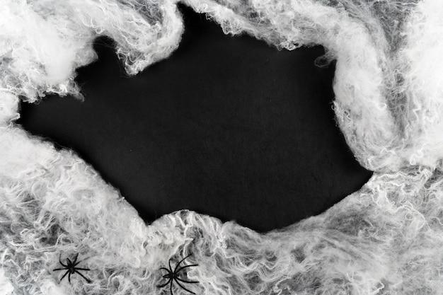 Plat lag halloween. spinnenwebben met spinnen op zwarte achtergrond met plaats voor tekst kopie ruimte.
