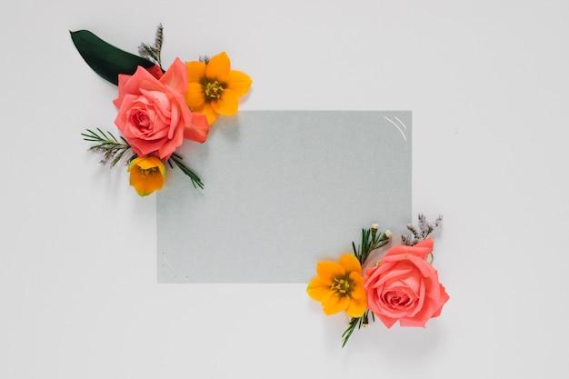 Plat lag helder creatief kader van verse bloemen en bladeren met grijs schoon kader voor natuurlijke tekst