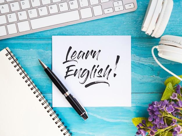 Plat lag het bestuderen van nieuwe taalhulpmiddelen op blauwe houten achtergrond