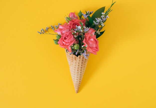 Plat lag ijsje met kleurrijke boeket op geel, kopie ruimte