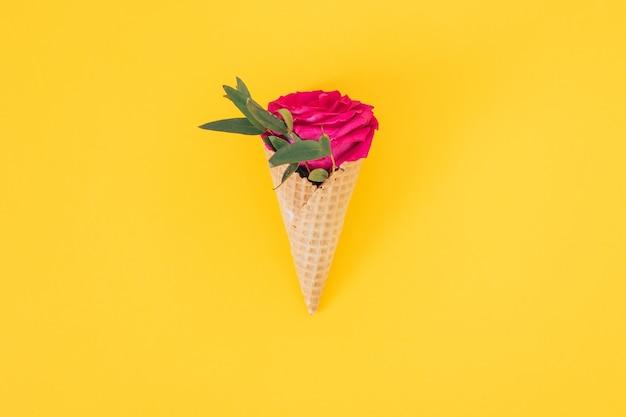 Plat lag ijsje met roze roos op geel, kopie ruimte