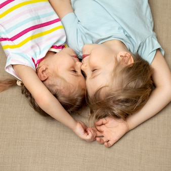 Plat lag jongen en meisje, zittend op de vloer