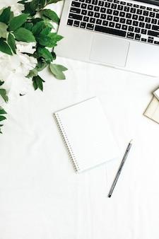 Plat lag kantoor aan huis bureau met laptop, notebook, witte pioenrozen bloemen boeket op wit oppervlak