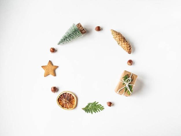 Plat lag kerst cirkel frame samenstelling - ster cookie, noten, cadeau, droge sinaasappel slice, kerstboom en dennentakken. bovenaanzicht, kopie ruimte