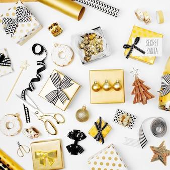 Plat lag kerst- of feestachtergrond met geschenkdozen, champagnefles, strikken, decoraties en inpakpapier in gouden en zwarte kleuren. platliggend, bovenaanzicht