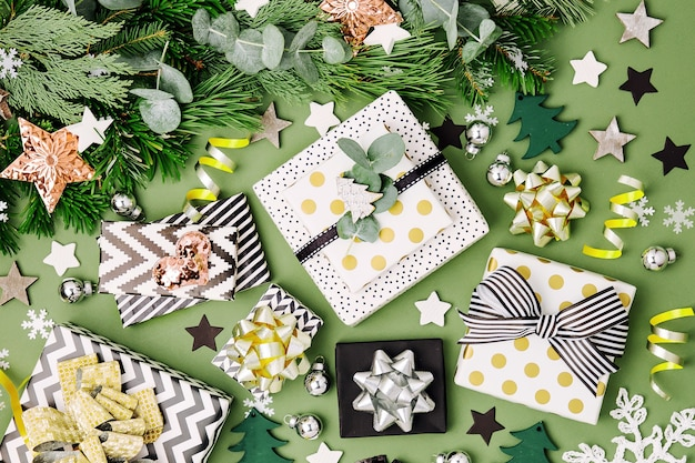 Plat lag kerstachtergrond met geschenkdozen, linten en decoraties in groene en zwarte kleuren. platliggend, bovenaanzicht