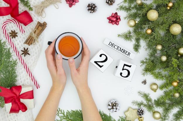 Plat lag kerstdecoratie en vrouw hand met kopje thee 25 dec eeuwigdurende kalender.