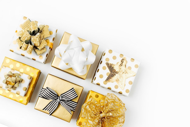Plat lag kerstmis of feest achtergrond met geschenkdozen en decoraties in gouden kleuren. platliggend, bovenaanzicht