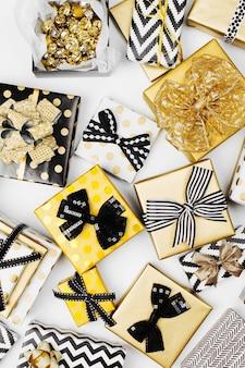 Plat lag kerstmis of feest achtergrond met geschenkdozen, linten, decoraties in goud en zwart kleuren. platliggend, bovenaanzicht