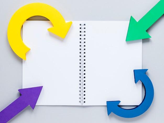 Plat lag kleurrijke pijlen en notebook-model op witte achtergrond