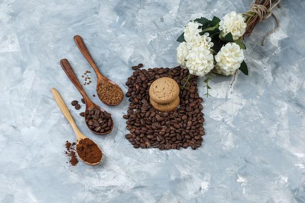 Plat lag koekjes met koffiebonen, oploskoffie, koffiemeel in houten lepels, bloemen op lichtblauwe marmeren achtergrond. horizontaal