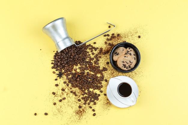 Plat lag koffiebonen in kruik met glazen pot, kopje koffie, chocoladeschilferkoekjes op gele achtergrond. horizontaal