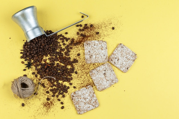 Plat lag koffiebonen in kruik met rijstwafels, touwen op gele achtergrond. horizontaal