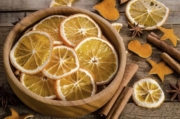 Plat lag kruiden en volle kom met droge sinaasappel op hout