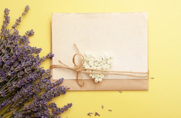 Plat lag leeg blad voor tekst met hart en lavendel bloemen op een gele achtergrond.