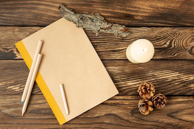 Plat lag leeg notitieboekje naast dennenappels