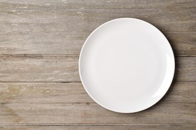Plat lag lege witte plaat op houten tafel.