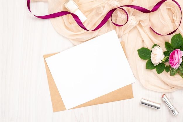 Plat lag lege witte wenskaart met ambachtelijke papieren envelop, rozen bloemen, lippenstift, lint