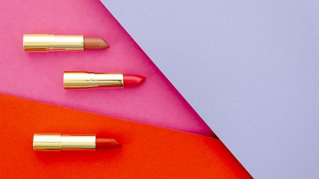Plat lag lippenstiften op kleurrijke achtergrond