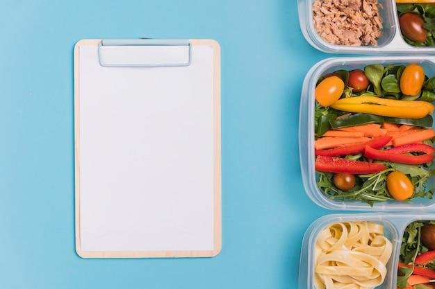 Plat lag lunchboxen met lege notebook