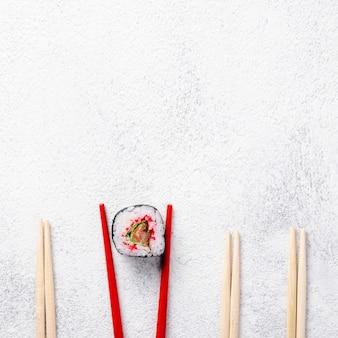 Plat lag maki sushi roll en eetstokjes met kopie ruimte