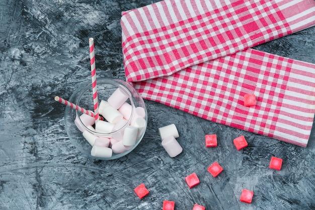 Plat lag marshmallows en suikerriet in pot met snoepjes en rood pastel tafelkleed op donkerblauw marmeren oppervlak. horizontaal