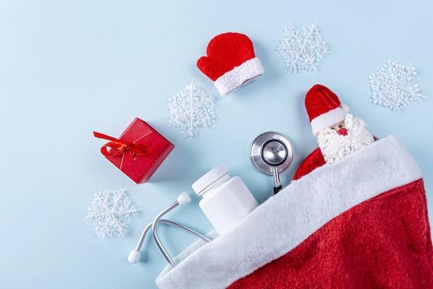 Plat lag medische nieuwjaars samenstelling met stethoscoop, pillen, geschenkdoos en kerstdecoratie