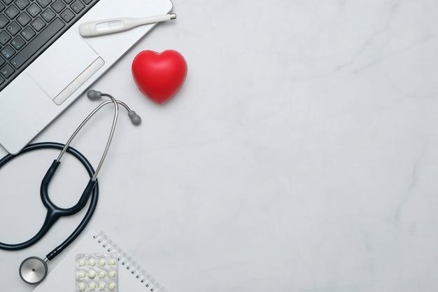 Plat lag met arts bureau tafel met stethoscoop, notebook, kantoorbenodigdheden en kopie ruimte