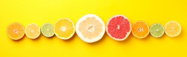 Plat lag met citrusvruchten op gele achtergrond, ruimte voor tekst