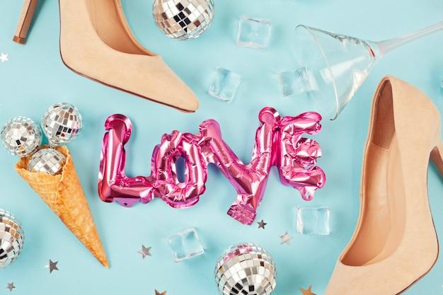 Plat lag met damesschoenen, discoballen, ijsblokjes, cocktailglas en confetti.