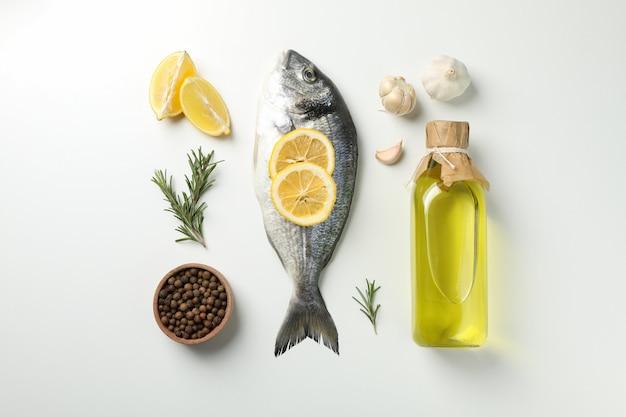 Plat lag met dorado vis en koken ingrediënten op witte achtergrond, bovenaanzicht Premium Foto
