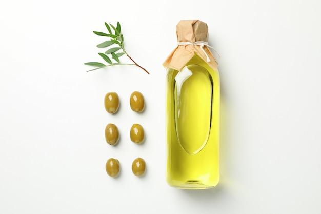Plat lag met fles olijfolie, olijven en bladeren op wit, ruimte voor tekst