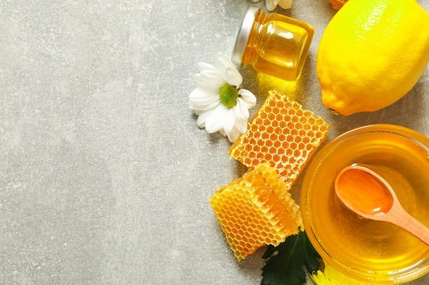 Plat lag met honing, bloemen en fruit op grijze achtergrond, kopie ruimte