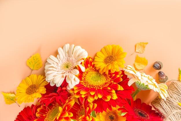 Plat lag met kleurrijke rood geeloranje herfstbloemen op beige warm gekleurde achtergrond. bright fall, thanksgiving day concept. bovenaanzicht, kopieer ruimte