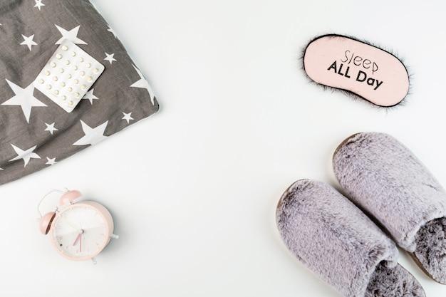 Plat lag met slippers, kussen, blinddoek, pillen en wekker