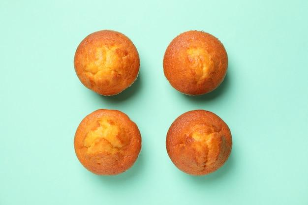Plat lag met smakelijke muffins op mint achtergrond, bovenaanzicht
