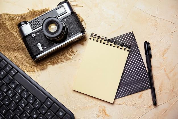 Plat lag met spiraalvormige notitieblok-toetsenbordpen en oude camera op gestructureerde beige achtergrond
