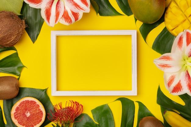 Plat lag met tropische vruchten, planten en foto frame achtergrond