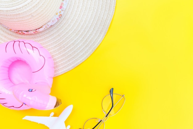 Plat lag met vliegtuig zonnebril, hoed en opblaasbare flamingo geïsoleerd op gele achtergrond on