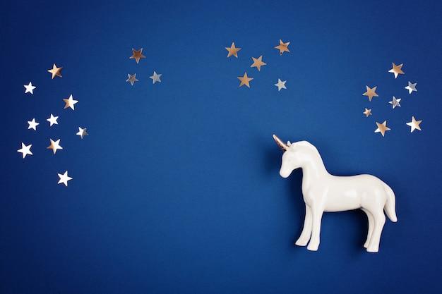 Plat lag met witte eenhoorn en sterren op de blauwe achtergrond