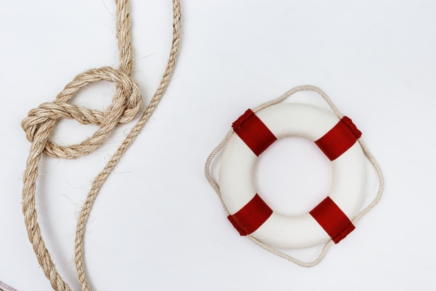 Plat lag met zee touw knoop en reddingsboei op wit kopieer ruimte.