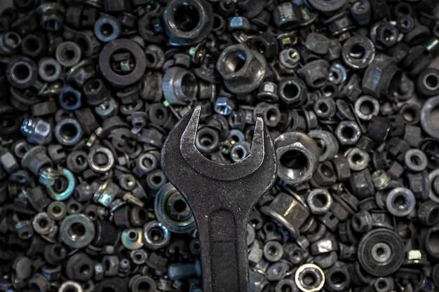 Plat lag metalen sleutels op de achtergrond van verschillende metalen tandwielen, schroeven en spijkers, bovenaanzicht.