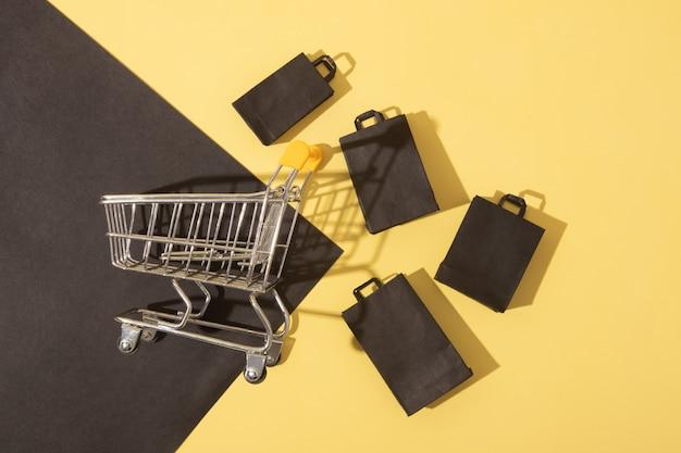 Plat lag miniatuur supermarktkarretje met boodschappentassen in black friday sale op gele achtergrond
