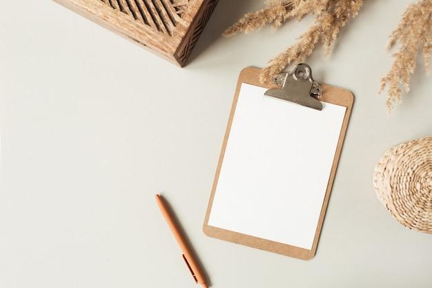 Plat lag minimalistisch thuiskantoor met blanco bladklembord met kopie ruimte voor tekst, riettak, kistje op neutraal oppervlak